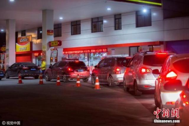 ↑资料图:众多车主在国内某地加油站排队加油。