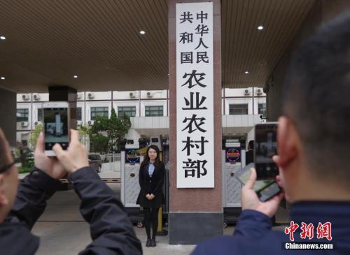资料图:4月3日,新组建的中华人民共和国农业农村部在北京正式挂牌,民众争相与新牌合影。 中新社记者 贾天勇 摄