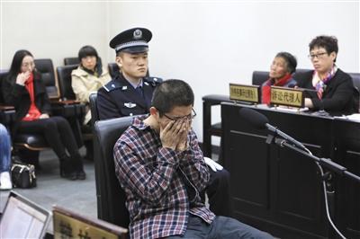 昨日,41岁的朱某受审时,听到律师辩护提及其家中上有老下有小时捂住了脸。1997年,朱某参与一起打架事件导致一人死亡,之后变换身份潜逃20年。 新京报记者 王嘉宁 摄