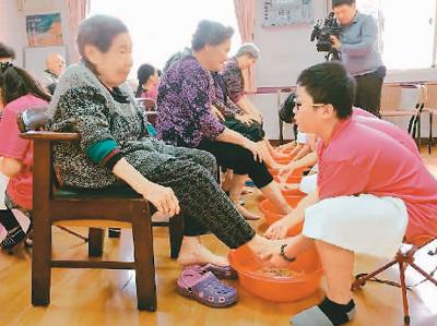 新北市万里区大坪小学规划公益毕业旅行,学生为年长者洗脚。(图片来源于大坪小学)