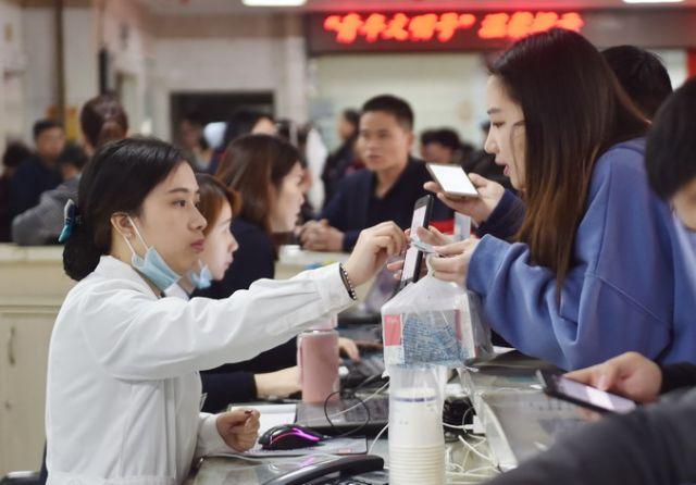 2018年3月22日,在福建医科大学附属第一医院,患者向工作人员出示手机预约挂号信息。(新华社记者宋为伟 摄)