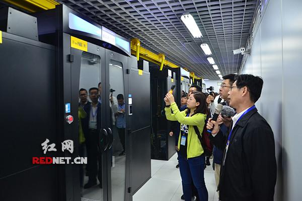 蔡荣富(右一)向记者介绍福建省电子政务云平台运行情况。红网 图