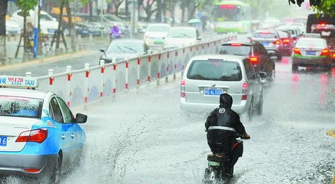 市民冒着大雨出行。