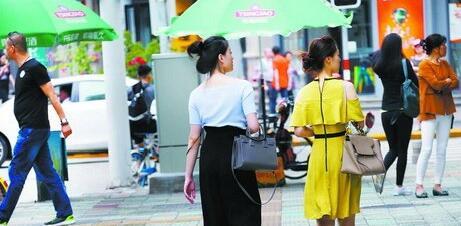 冷空气影响消退,夏装又回来了。图为10日下午街头行人
