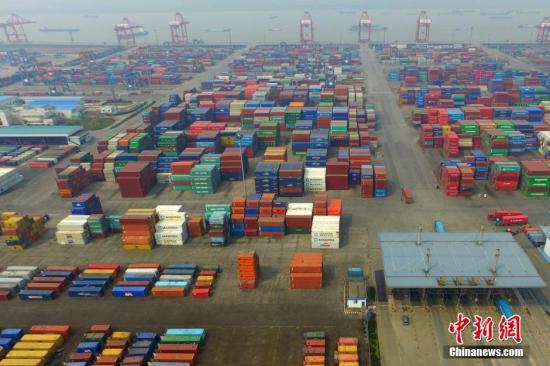 资料图:贸易繁荣,中国某港口不同颜色的集装箱犹如积木般堆砌在一起。中新社记者 泱波 摄