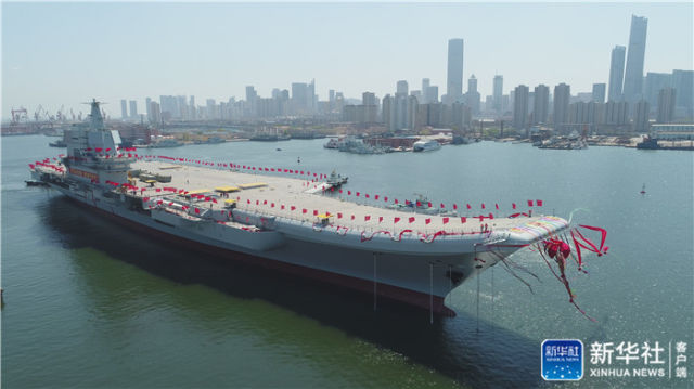 ↑图为航空母舰在拖曳牵引下缓缓移出船坞,停靠码头。新华社记者 李刚 摄