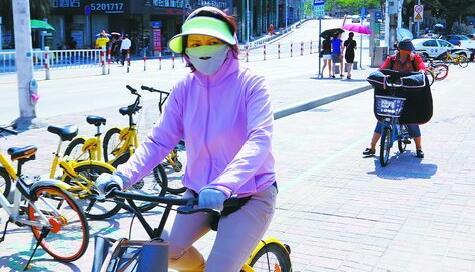 """昨日下午,中山公园南门附近,一位骑车的市民""""全副武装""""防晒。"""