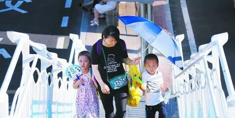 天气炎热,市民携带伞和扇子出行。