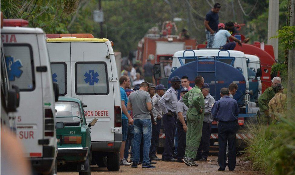 坠毁现场有浓烟,消防队员和救护车都在现场。