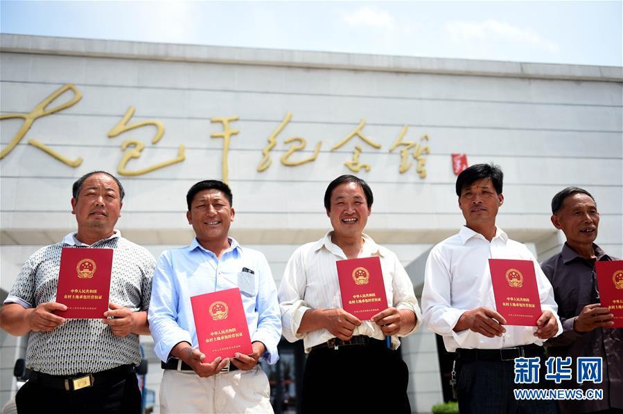 安徽凤阳县小岗村农民展示领到的《农村土地承包经营权证》(2015年7月8日摄)。 新华社记者 刘军喜 摄