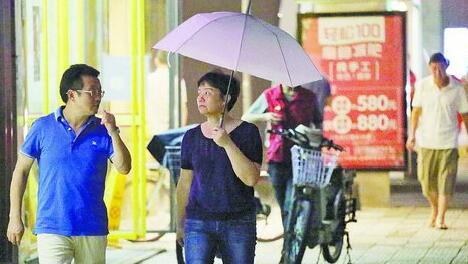 昨日我市有阵雨,图为昨晚街头打伞行人