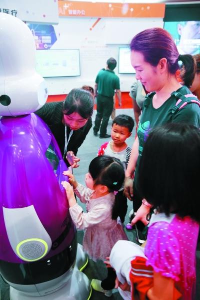 儿童观众与展厅人工智能小I机器人互动。