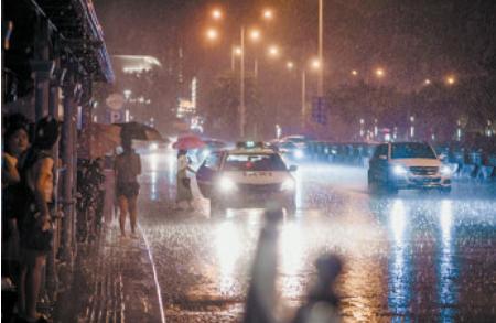 大雨突然来袭,路人急忙躲在公交站点避雨。