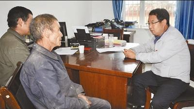 李培东(右一)在与党员们谈心。资料照片