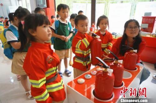 资料图:儿童节孩子们穿上迷你消防服,体验模拟灭火。 韩章云 摄