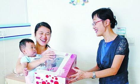 市卫生计生委副主任王挹青(右)向住院患儿赠送儿童节礼物