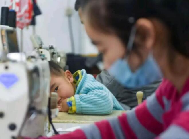 1月11日,在福建省石狮市金利莱斯服装厂,聪聪望着在一旁忙碌的母亲黄爱华。