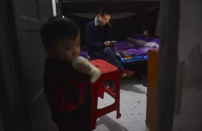 1月31日,在福建省石狮市金利莱斯服装厂工人宿舍,聪聪的父母黄海龙(中)、黄爱华忙碌了一天正在休息,聪聪在宿舍门口喝奶。