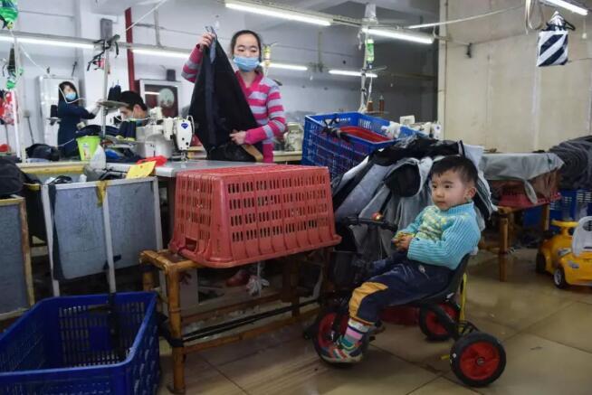 1月11日,在福建省石狮市金利莱斯服装厂,黄爱华(右二)在工作之余照看在旁边骑玩具车的聪聪。
