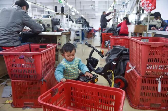 1月11日,在福建省石狮市金利莱斯服装厂,聪聪在父亲黄海龙(左)的工位旁玩玩具车。