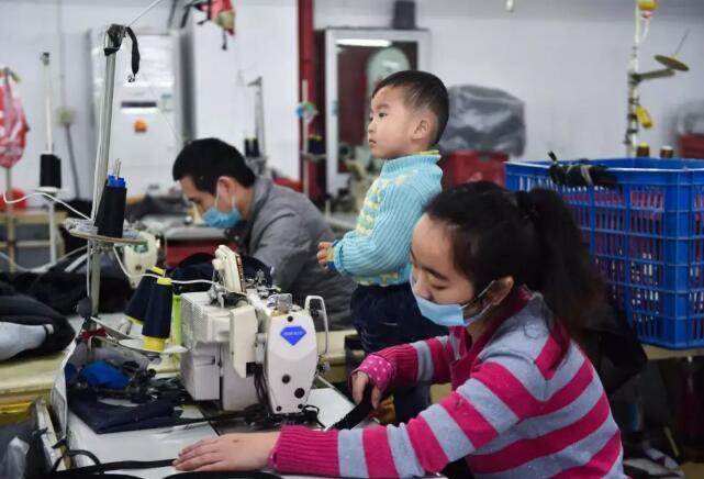 1月11日,在福建省石狮市金利莱斯服装厂,聪聪在陪伴父亲黄海龙(左)、母亲黄爱华上班。