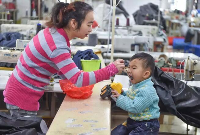 1月11日,在福建省石狮市金利莱斯服装厂,聪聪的母亲黄爱华在给聪聪喂午饭。