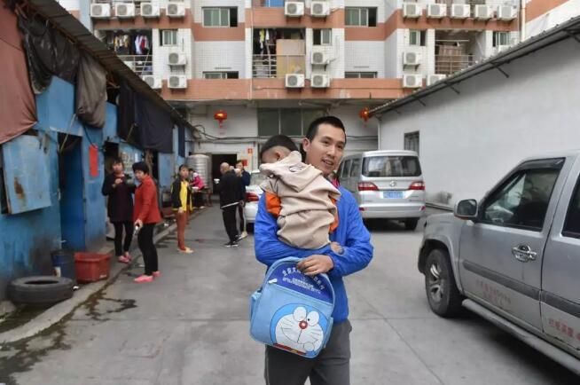 4月18日,在福建省石狮市金利莱斯服装厂,黄海龙抱着睡眼惺忪的聪聪走出工厂,准备乘坐校车去幼儿园。