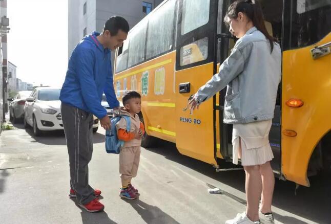 4月18日,在福建省石狮市金利莱斯服装厂门口,黄海龙(左)将聪聪送上去往幼儿园的校车。