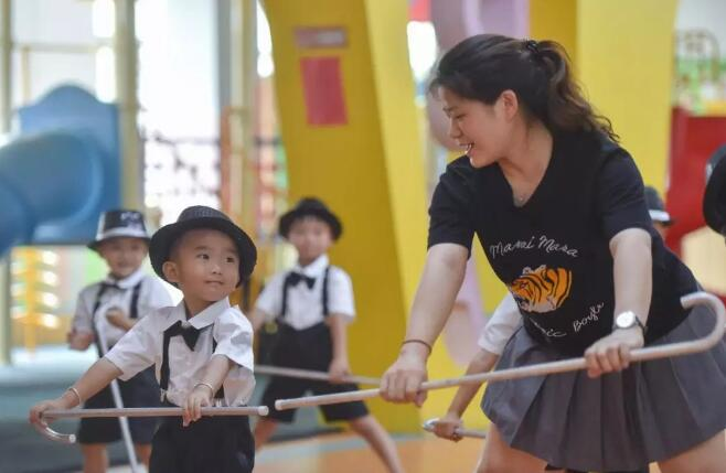"""5月31日,在福建省石狮市鹏博幼儿园,聪聪(左)跟着老师林慧芬排练""""六一""""节目。"""
