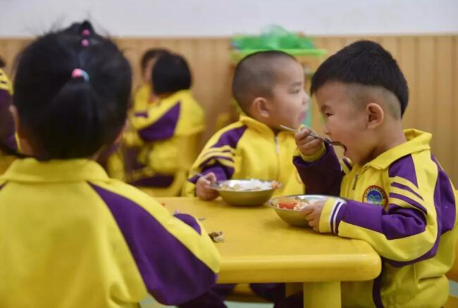 4月17日,在福建省石狮市鹏博幼儿园,刚刚入园一个月的聪聪(右一)在吃饭。