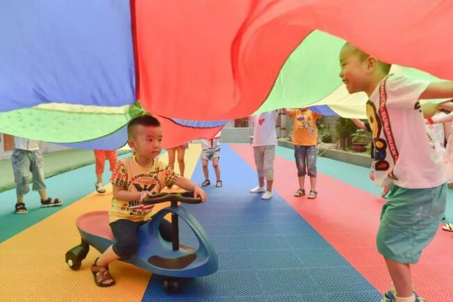 5月31日,在福建省石狮市鹏博幼儿园,聪聪(左)和同学们玩游戏。