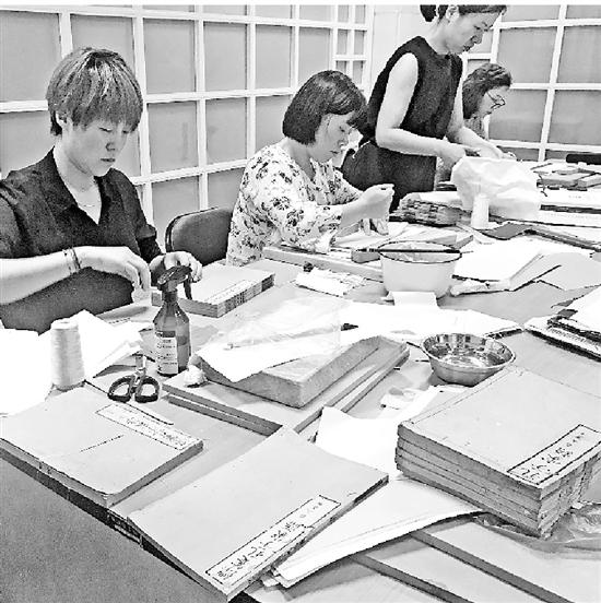 修复师们正在修复读者送来的古籍。