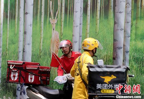 资料图:5月23日,北京西单街头的外卖骑手准备送餐。 中新社记者 张宇 摄