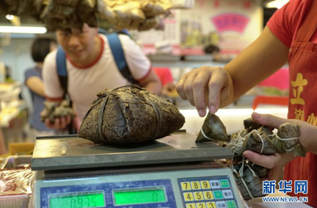 """6月5日拍摄的台北南门市场""""立家""""粽子摊里最大的粽子和最小的粽子。新华社记者 林善传 摄"""