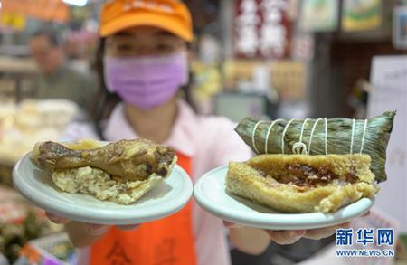 """6月5日,台北南门市场""""合兴""""粽子摊的员工展示""""鸡腿棒棒粽""""(左)和肉粽。新华社记者 林善传 摄"""
