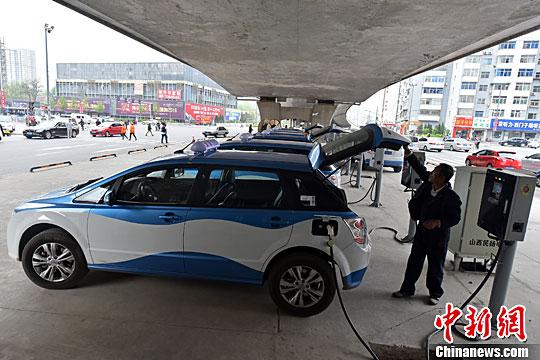 资料图:电动汽车在充电桩旁充电。中新社记者 武俊杰 摄