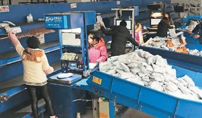 某快递网点的员工在为一批电商邮件称重发货。