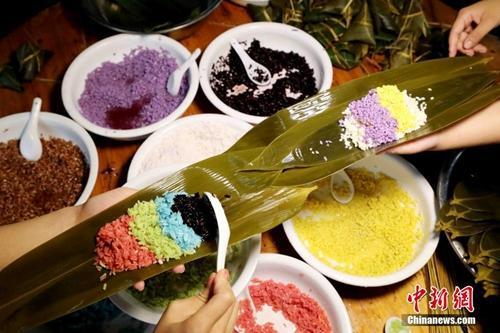 资料图:广西山区壮族同胞赶制五彩粽子迎端午。