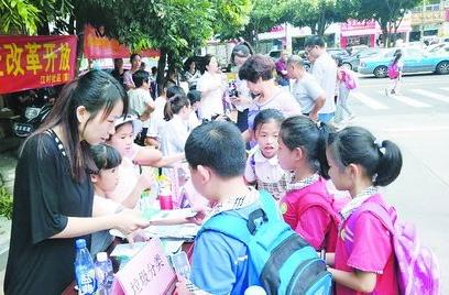 江村社区工作人员分发垃圾分类宣传材料。
