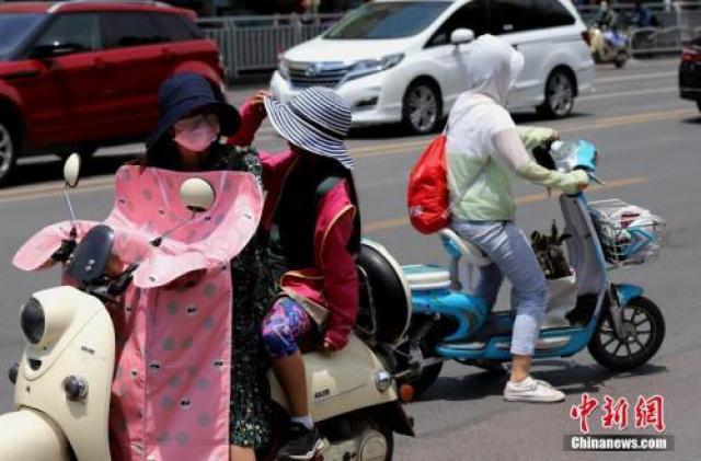 """↑资料图:6月6日,河南郑州遭遇高温天气,出行民众""""全副武装""""遮阳防晒。"""