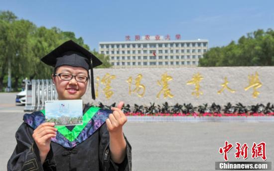 毕业生拿着手绘校园景色明信片合影。 (中新社记者 于海洋 摄)