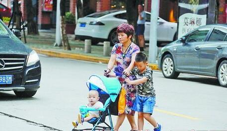 昨天,厦门阴有阵雨,街头行人匆匆过马路。