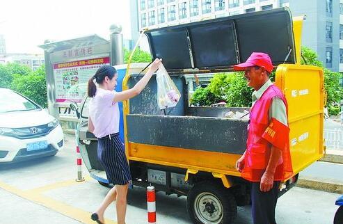 """江头街道试点""""无垃圾桶""""小区,居民定时定点把垃圾投入垃圾车。"""