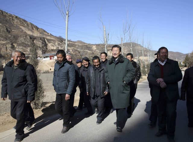 2015年2月13日至16日,习近平在延安市延川县文安驿镇梁家河村调研时同村民边走边聊。