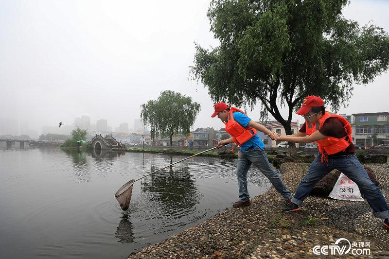 红领之家志愿者打扫水面垃圾。(资料图片)