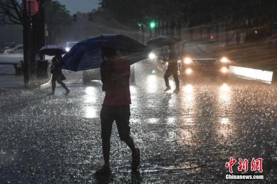 资料图:民众撑伞行走在雨中。中新社记者 陈骥旻 摄