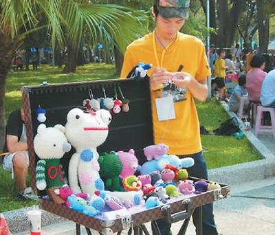 用钩针编制艺术品的街头艺人。记者 吴亚明 摄