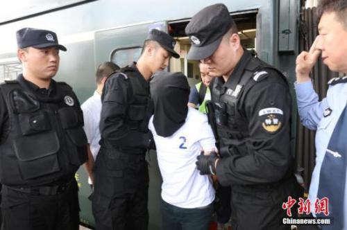 """2018年5月29日,黑龙江省警方押解124名""""5.6""""特大系列电信诈骗案犯罪嫌疑人抵达哈尔滨。中新社记者 于琨 摄"""