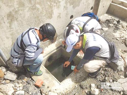 台湾高雄市环保局人员协助防治登革热,日前到工地水泥槽检查积水情况。台湾《中国时报》记者林瑞益翻摄