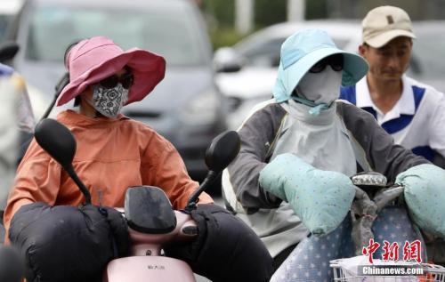 """7月16日,南京市民""""全副武装""""骑车出行。当日,南京继续高温晴热天气。中新社记者 泱波 摄"""